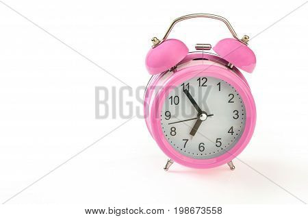 Retro pink alarm clock with 5 minutes to 7 o'clock on it. Isolated on white background