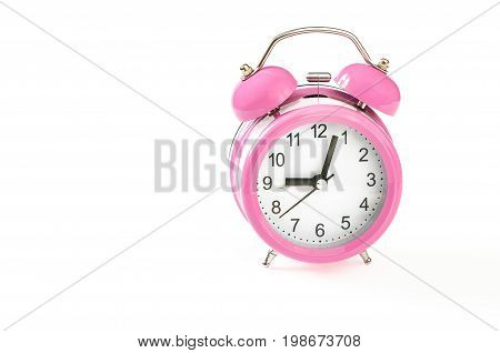 Vintage pink alarm clock with 3 minutes past 9 o'clock on it. Isolated on white background. Close up