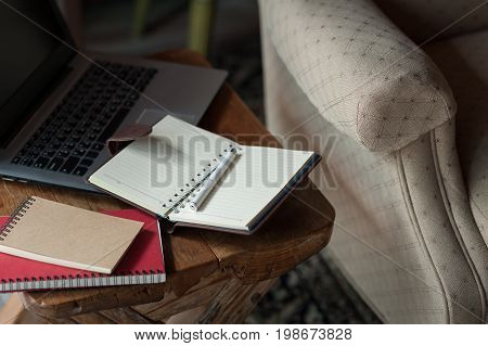 Pen notebooks and laptop computer on small wood table. Working at home on weekend concept