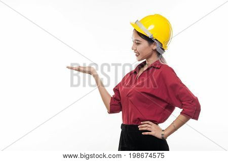 Asian woman engineer in red shirt and yellow safety cap smiling while showing palm hand. People gesturing in business and enginerring concept