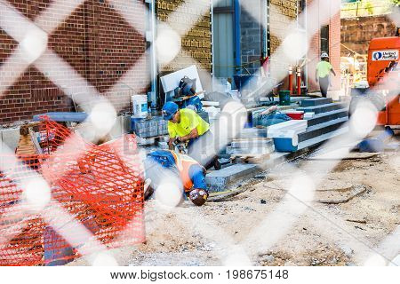 Washington DC USA - July 3 2017: Construction workers behind fence area digging in ground repairing floor and staircase