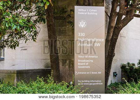 Washington DC USA - July 3 2017: Sign for Voice of America and Broadcasting Board of Governers Wilbur J. Cohen building in downtown