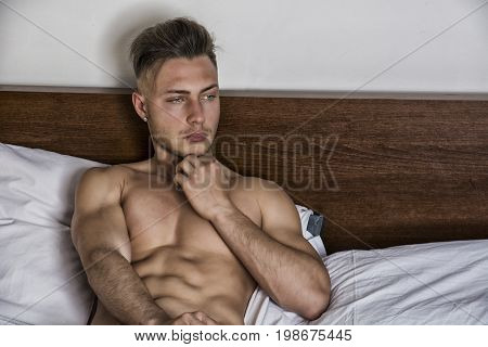 Totally naked sexy young man with muscular body on bed looking away