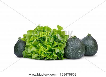A group of three round saturated green zucchinis isolated over the white background. Ripe and raw zucchinis with salad leaves for natural organic salads. Vegetables for various vegetarian snacks.