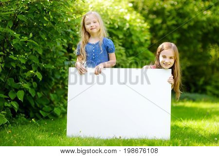 Two Cute Little Sisters Holding Big Blank Whiteboard On Sunny Summer Day Outdoors