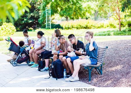 Washington DC USA - July 3 2017: People eating fast food on sidewalk bench from food trucks on street by National Mall on Independence Avenue
