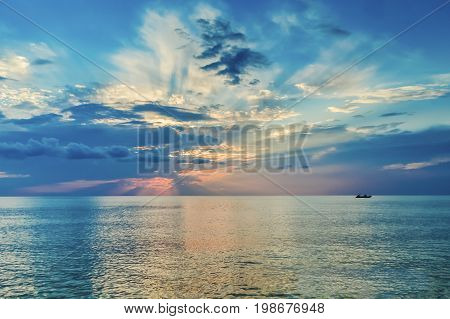 Beautiful sunset over the sea. The setting sun in a whimsical pattern of clouds. Greece.
