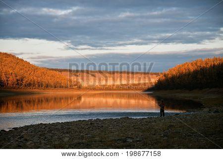 Evening fishing on the Siberian taiga river Moiero in the fall. Evenkiya Krasnoyarsk region Russia