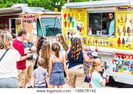 Washington DC USA - July 3 2017: Food trucks on street by Ice Cream storefront on Independence Avenue and people in queue buying