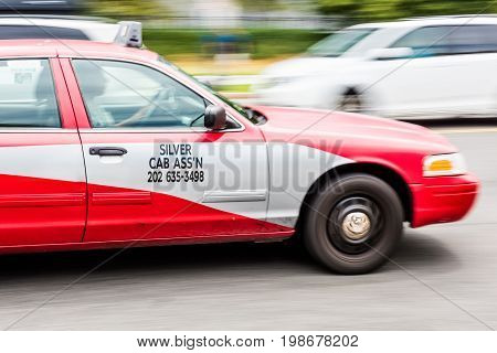 Washington DC USA - July 3 2017: Panning shot of red taxi cab on the streets with Silver Cab Assistant sign and number