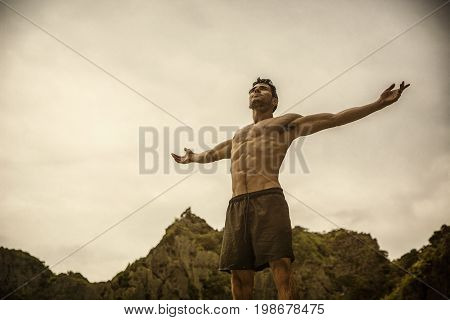 Muscular young man on the beach, with arms open enjoying the sensation of freedom in front of rising or setting sun