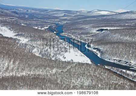 Mountain range after a snowfall and the river in the spring of Kamchatka. The view from the helicopter on the forest and the river in may in far East Russia.