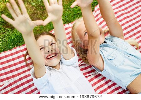 Ecstatic girls raising their hands while having fun outdoors