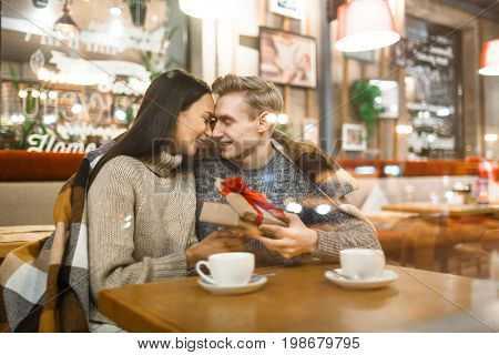 Amorous couple celebrating their dating anniversary in small cafe