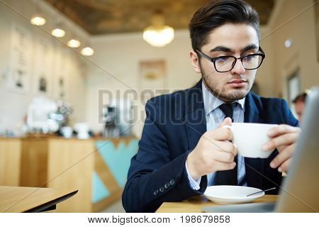Serious specialist with cup of coffee searching prestigious job for himself in front of laptop