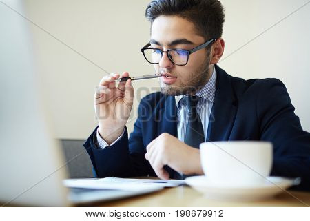 Financial director contemplating with pen in mouth while reading document or contract