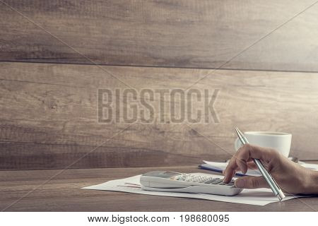 Side View Of Accountant Balancing The Books With Calculator