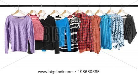 Set of shirts and blouses hanging on clothes racks isolated over white