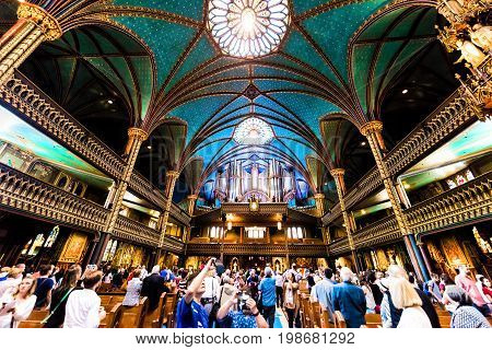 Montreal Canada - May 28 2017: Inside Notre Dame Basilica during mass with many people taking pictures of detailed architecture and organ