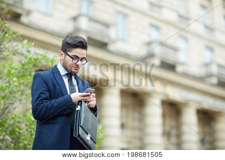 Man with briefcase reading sms in smartphone outdoors