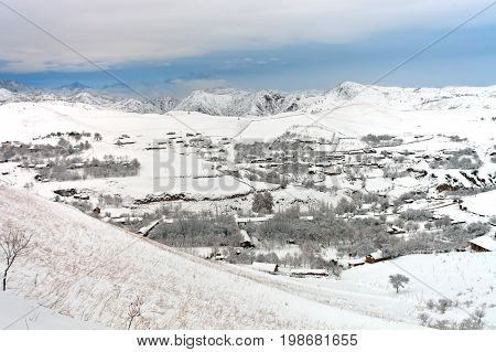 Village in the mountains of Tajikistan after a snowfall. Mountain village Mulkon in December