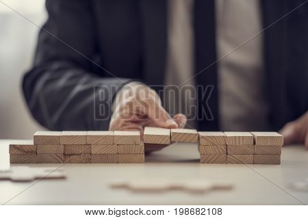 Close Up Of Fingers From Hand Of Business Man Assembling A Bridge