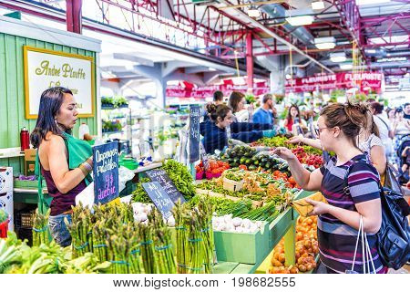 Montreal Canada - May 28 2017: Woman buying produce by fruit and vegetable stands at Jean-Talon farmers market with displays