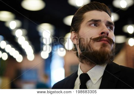 Posh man with beard and moustache on background of night lights