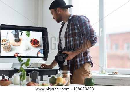Contemporary photographer looking through his shots in computer after shooting