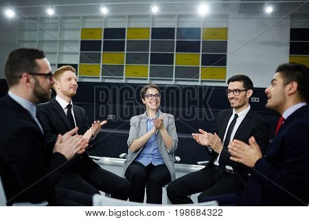 Business people gathered for meeting to discuss some changes in the company and clapping their hands after it