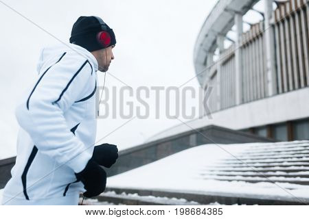Running guy in hoodie, beanie and gloves moving upstairs in urban environment