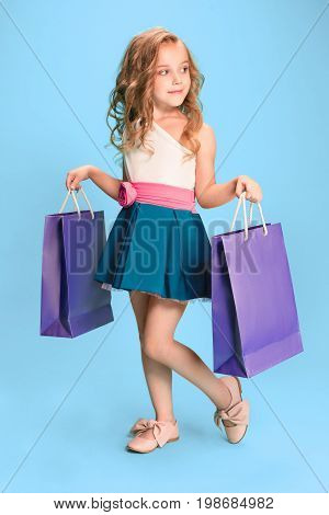 The cute little caucasian brunette girl in hat holding shopping bags on blue studio background