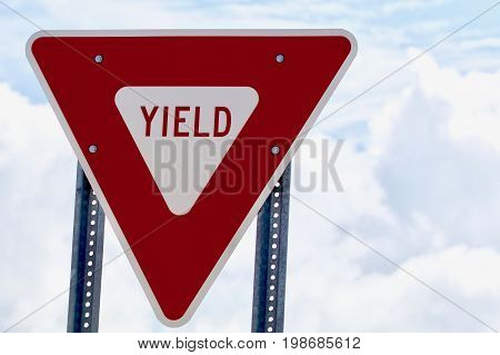 Red and White Yield Sign with clouds Horizontal