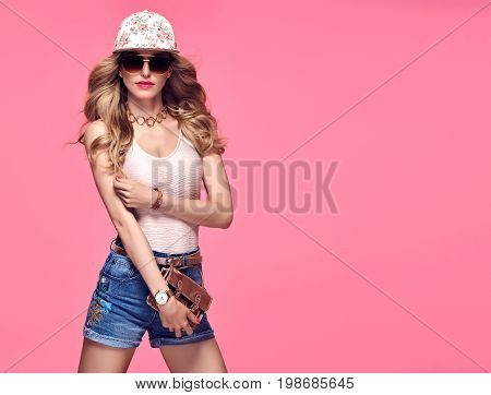 Fashion Model Sexy Girl. Stylish Summer Outfit. Hipster woman Cheeky emotion. Crazy Blond in Fashion Sunglasses, Glamour Denim Shorts.Trendy fashion Cap. Playful Summer Wavy Hairstyle