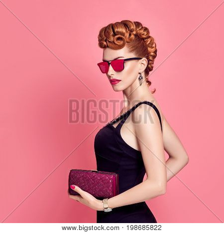 Fashion Model in Sexy Jumpsuit. Stylish Mohawk hairstyle, fashion Sunglasses, Summer Party Disco Outfit. Beauty Redhead Woman in Trendy Luxury Accessories. Glamour fashion Lady. Playful Girl on Pink