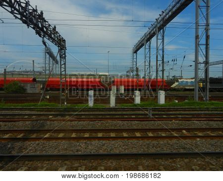 Red cargo train with electrical system and blue cloudy sky