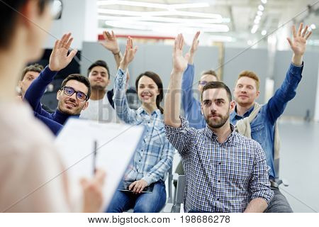 Confident business people raising hands to answer questions of lecturer of course