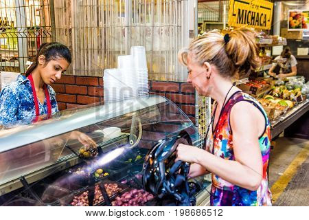 Montreal Canada - May 28 2017: Woman selling olives in Jean Talon market with people buying inside building in city in Quebec region