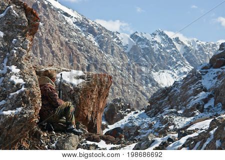 Hunter with a shotgun in the shelter among the rocks hunting in the Tien Shan mountains Kyrgyzstan.