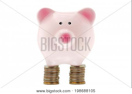 Pink ceramic piggybank standing on stack of many coins of the United States dollar, strong foundation of money saving, isolated on white
