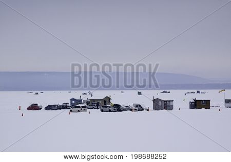 Wide view of a snow covered cars and fishing shacks on a frozen lake with mountains in the background near Hudson, Quebec on a bright overcast day in February.