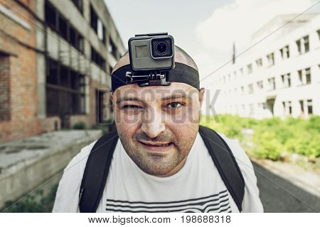 Angry man with action cam on head looking at camerao. Portrait of travel blogger in urban background, selective focus, toned