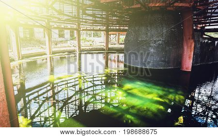 Water reservoir with green water of abandoned cooling tower in sun light, toned