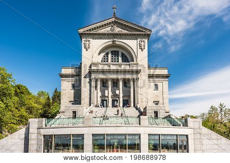 Montreal Canada - May 28 2017: St Joseph's Oratory on Mont Royal with sign and closeup of balcony terrace in Quebec region city with people sitting