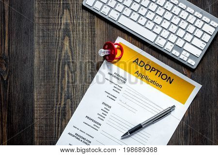 Adoption application on dark wooden table background top view.