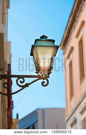 Street lamp of vintage design lighted on the wall in the afternoon.Syros island Greece