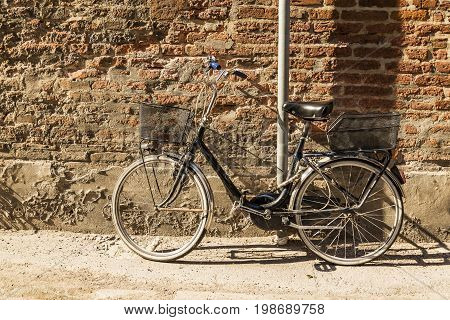 Old bicycle parked on a building wall in Ravenna, Italy