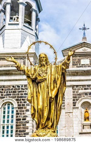 Champlain Canada - May 29 2017: Notre Dame de la Visitation stone church in small town on Chemin du Roy with gold Jesus Christ statue