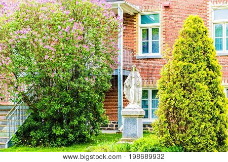 Champlain Canada - May 29 2017: Brick church in small town on Chemin du Roy with statue of Virgin Mary in summer