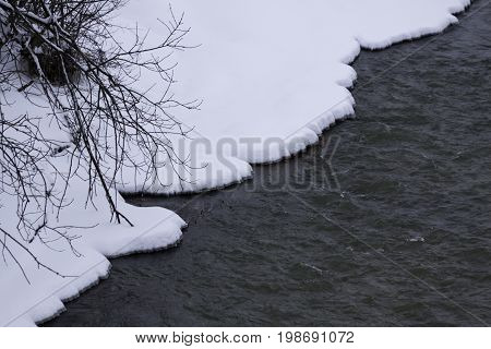 Wide view of a well defined snow covered shore line running diagonal along a small river near Hudson, Quebec on a bright overcast day in February.